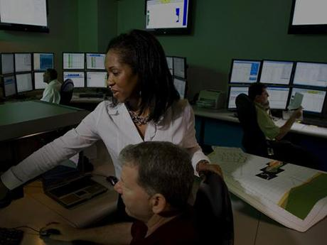 Photo of two Baker Hughes employees looking at computer screens