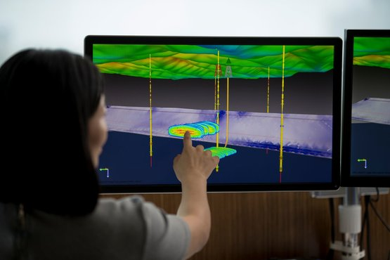 a woman analyzing seismic data on a touchscreen