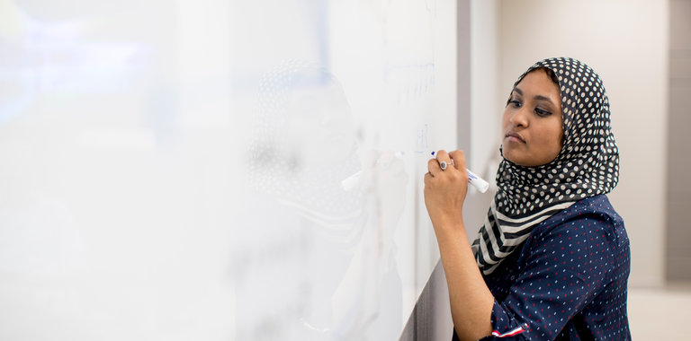 Photo of a woman writing on a whiteboard