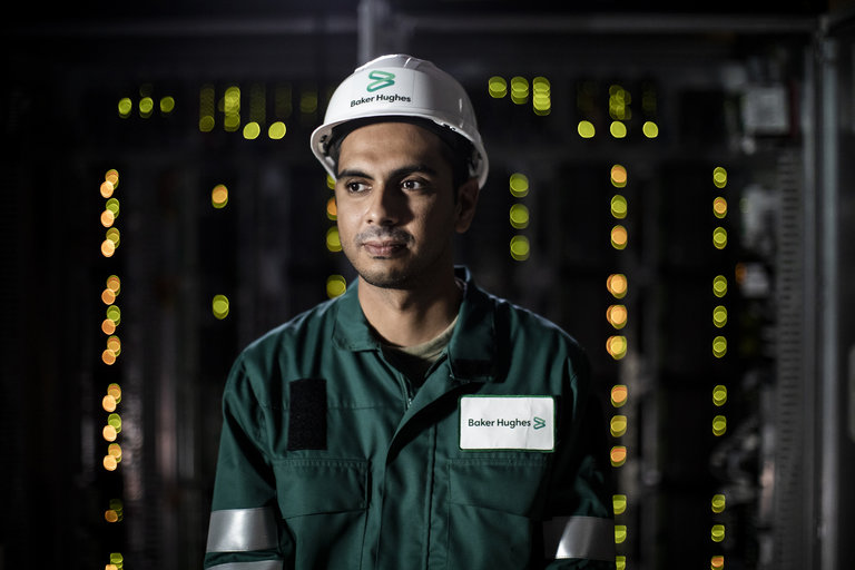 Portrait of a Baker Hughes employee in PPE in front of equipment