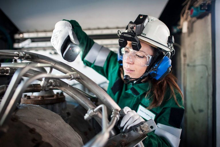 a woman in PPE inspecting equipment on site